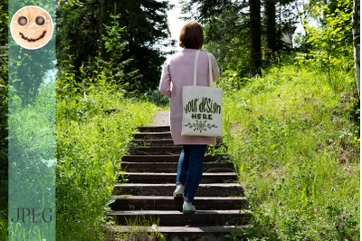 Woman on the old stair holding tote bag mockup