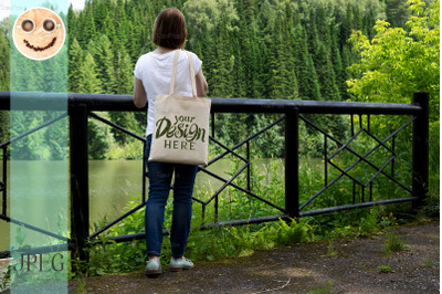 Woman in white tee holding tote bag mockup.