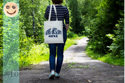 Woman in striped t-shirt holding tote bag mockup.