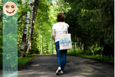 Woman in the park holding tote bag mockup.