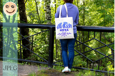Woman in blue jumper holding tote bag mockup