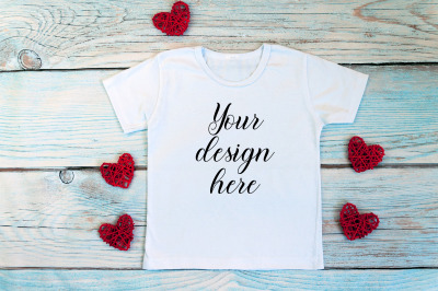 Valentines Day kids t-shirt mockup on a wooden background.