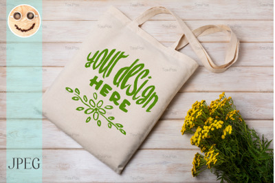 Rustic tote bag mockup with yellow wildflowers.