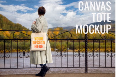 Woman in classic trench coat holding tote bag mockup.