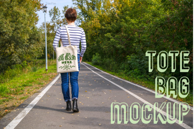 Woman holding tote bag walking in the park mockup.