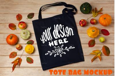 Black tote bag mockup with pumpkins and apples.