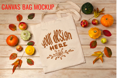 Rustic tote bag mockup with pumpkins and fall leaves.