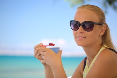 Young woman eating ice-cream on the beach