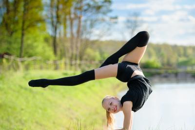Rhythmic gymnast girl exercising with ribbon outdoor