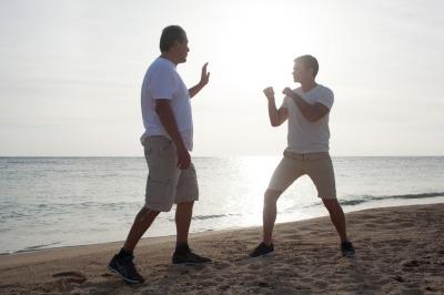 Two men having boxing training on the beach