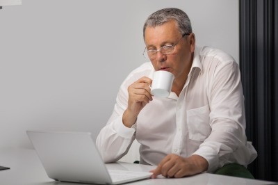 Businessman drinking coffee while working in office