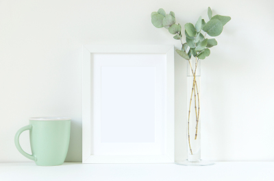 Styled stock white frame mockup with eucalyptus