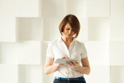 Businesswoman standing against white wall while looking at tablet