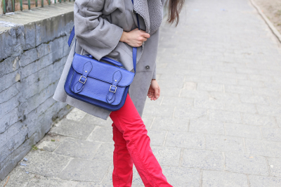 Woman in red jeans with blue leather handbag
