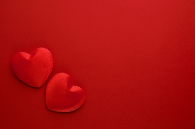 Two decorative hearts are on red paper. Flat lay