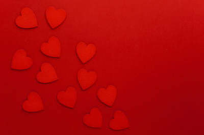 Decorative hearts are on red paper. Flat lay.