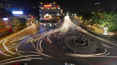 City square with traffic in motion at night. Hanoi, Vietnam