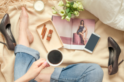 Girl with coffee mug in a bed