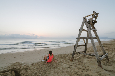 Girl watching the sunrise sitting on the beach