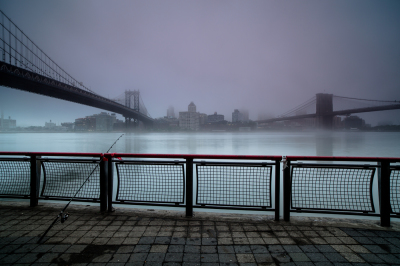 Foggy morning at the pier in Manhattan ,with fishing rod on a pier