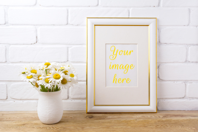 Gold decorated frame mockup with chamomile bouquet in rustic vase.