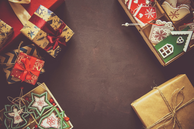 Christmas present boxes and box with wooden toys on brown background. Top view. Flat lay. Toned image