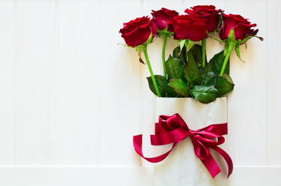 Valentine's day. Bag with burgundy roses on white wooden background. Top view