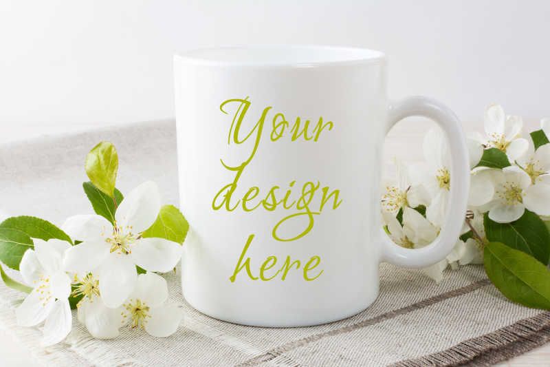 Free White coffee mug mockup with blossoming apple tree branch. (PSD Mockups)