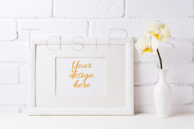 Free White frame mockup with soft yellow orchid in vase. (PSD Mockups)