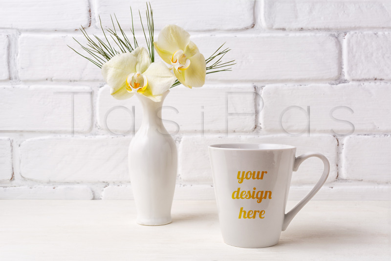 Free White coffee latte mug mockup with soft yellow orchid in vase. (PSD Mockups)