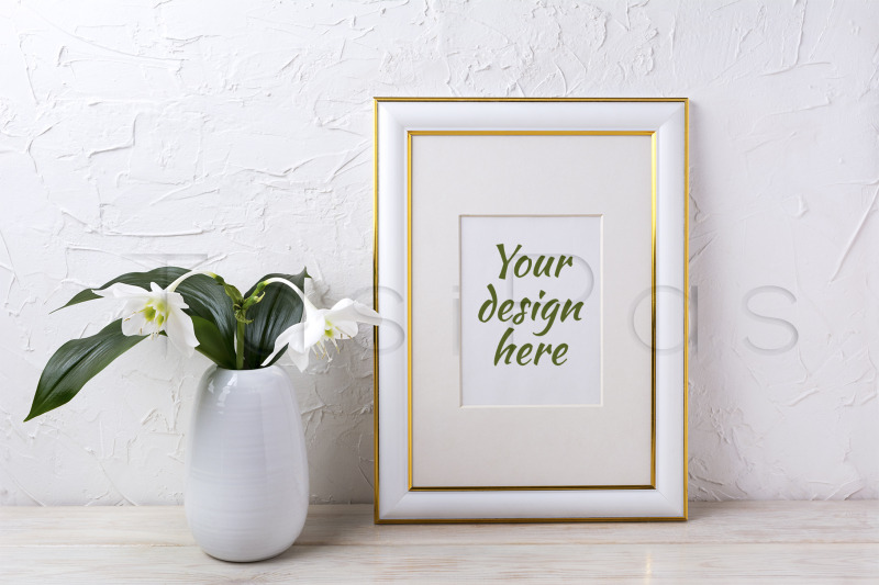 Free Gold decorated frame mockup with tender white lily in vase. (PSD Mockups)