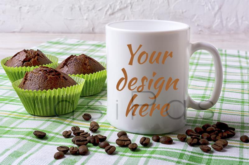 Free White mug mockup with chocolate muffins on green checkered napkin. (PSD Mockups)