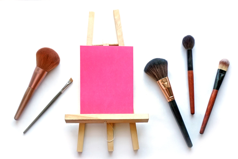 pink-card-on-the-easel-with-brushes-for-make-up-photo