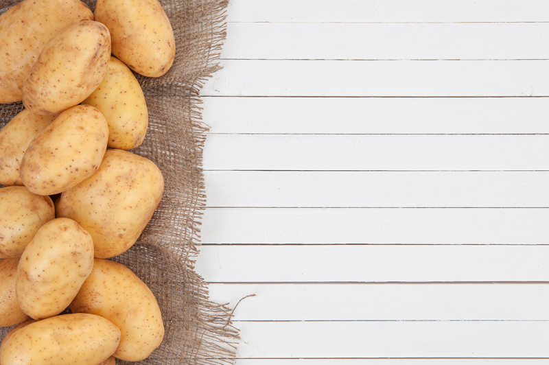 raw-potatoes-with-burlap-on-white-wooden-background-top-view