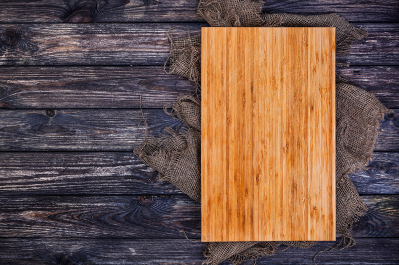 Free Cutting board on dark wood background, top view (PSD Mockups)