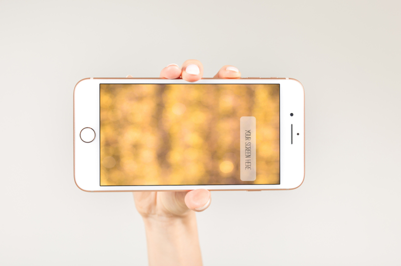 Free Female holding white smartphone with blank screen in here right hand (PSD Mockups)