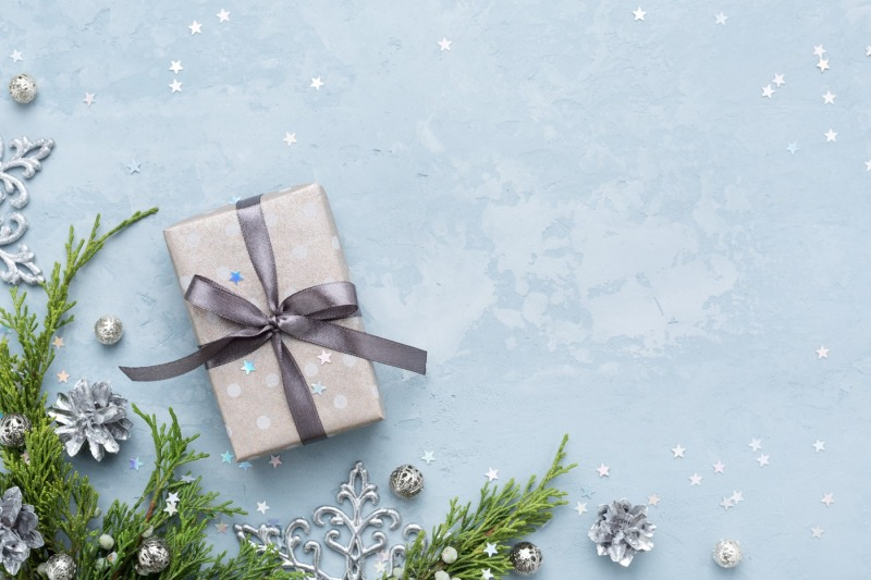 christmas-composition-with-evergreen-branches-and-gift-on-blue-space