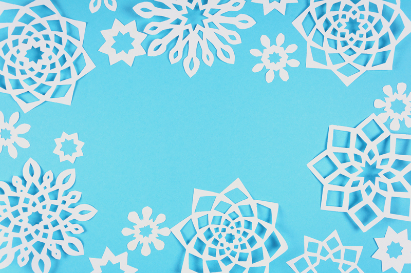 paper-snowflakes-on-blue-background-top-view-christmas-decoration