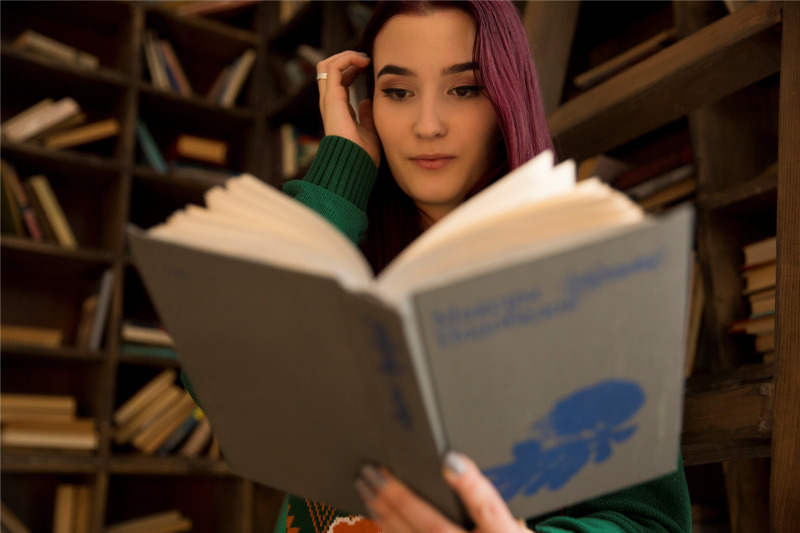 young-girl-reading-a-book-in-the-library