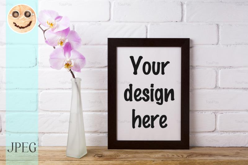 Free Black brown poster frame mockup with tender pink orchid (PSD Mockups)