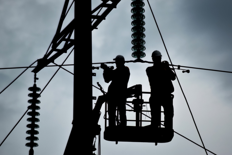 photo-silhouette-of-electricians-working-on-the-background-of-the-cloudy-sunset