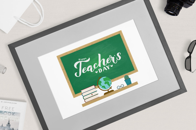 happy-teachers-day-calligraphy-hand-lettering-on-green-board-with-wood