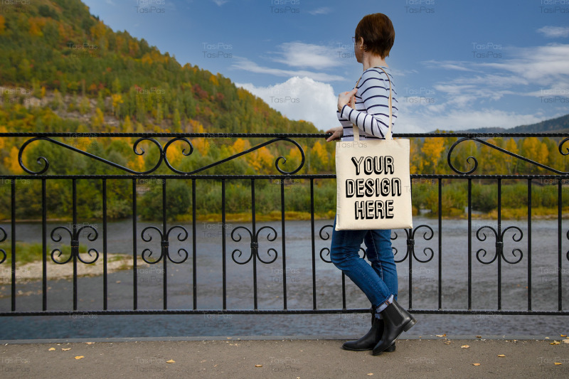 woman-in-striped-long-sleeve-shirt-holding-canvas-tote-mockup