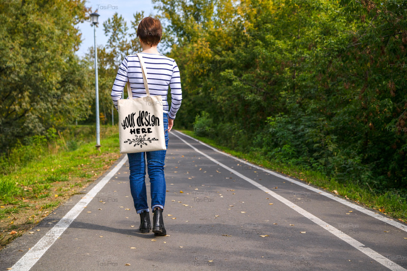 woman-holding-tote-bag-walking-in-the-park-mockup