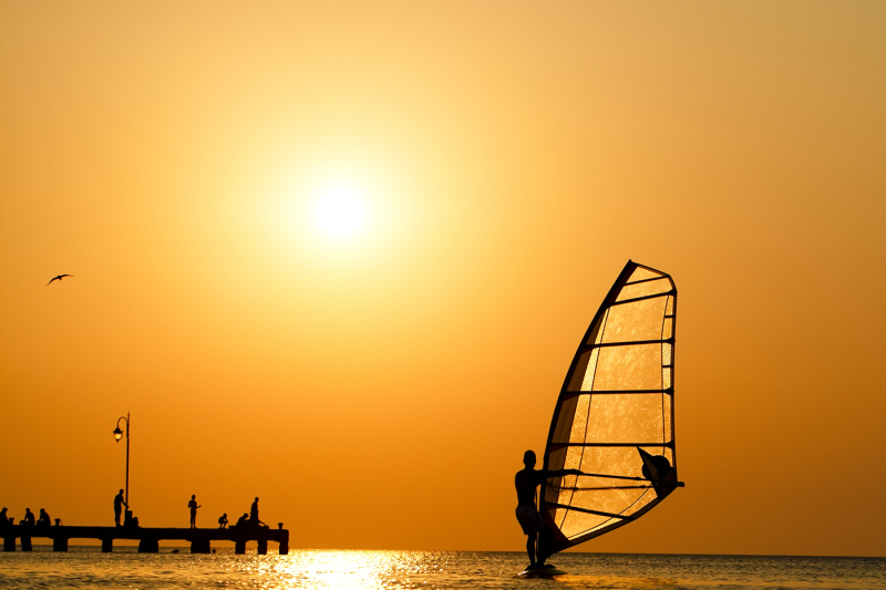 silhouette-of-surfer-at-sunset-passing-by