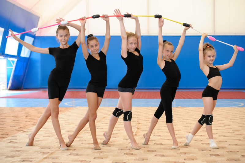 young-female-gymnasts-making-bow-with-indian-clubs