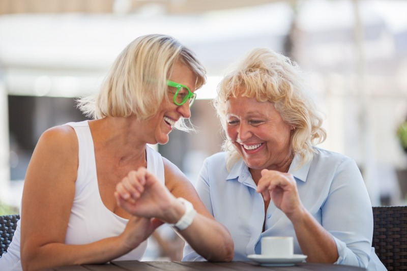 senior-women-laughing-in-street-cafe