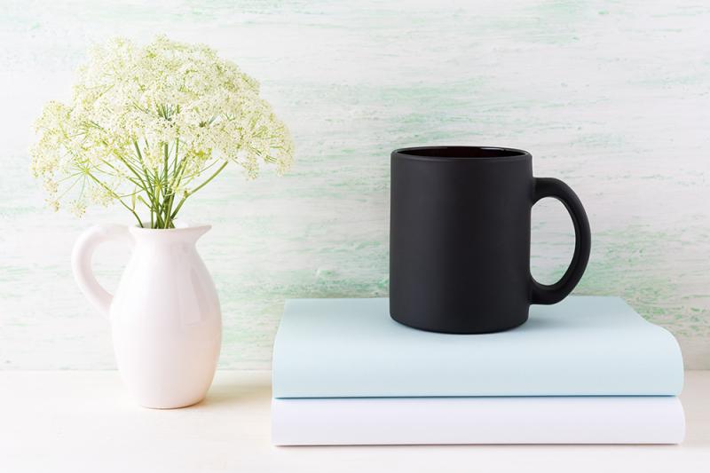 Free Black coffee mug mockup with books and tender white flowers (PSD Mockups)