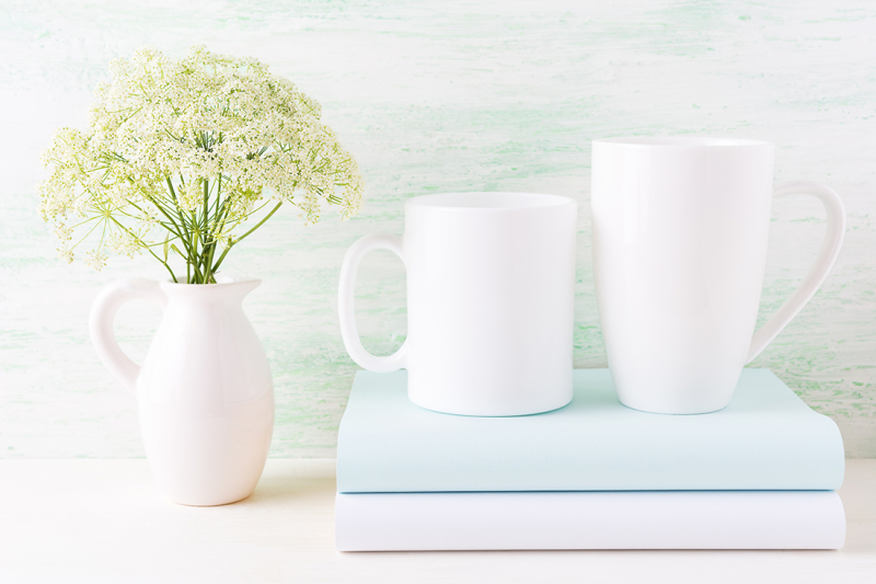 Free Two white mugs mockup with books and white flowers in pitcher (PSD Mockups)