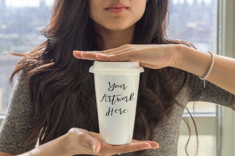Free Woman holding travel mug (PSD Mockups)